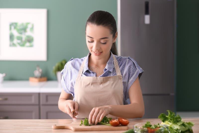 Młodej kobiety tnąca pietruszka dla sałatki w kuchni obraz stock