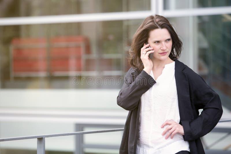 Młodej kobiety trwanie outside i opowiadać na telefonie fotografia stock