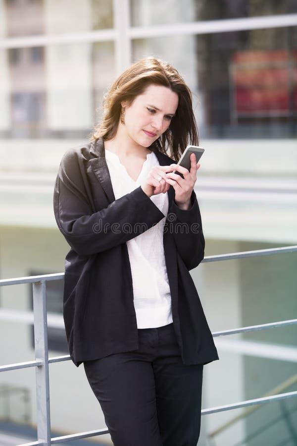 Młodej kobiety trwanie outside i texting na telefonie obraz stock