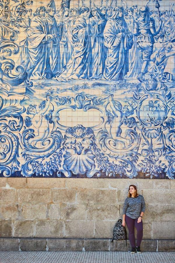 Młodej kobiety turystyczny odprowadzenie blisko kościół z sławnymi portuguese błękitnymi ceramicznymi płytkami na fasadzie podróż fotografia stock