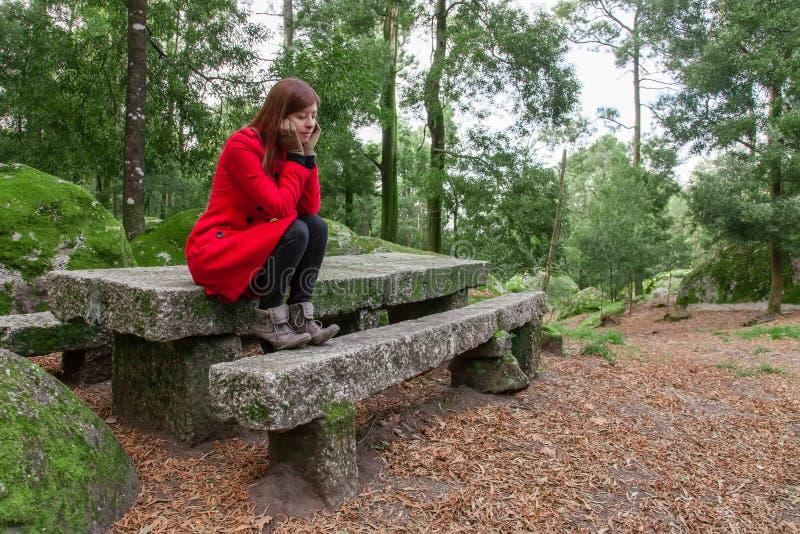 Młodej kobiety uczucia przygnębiony obsiadanie na lesie fotografia stock