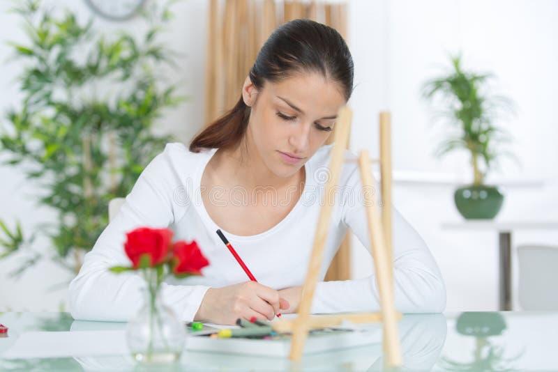 Młodej kobiety writing przy stołem fotografia stock