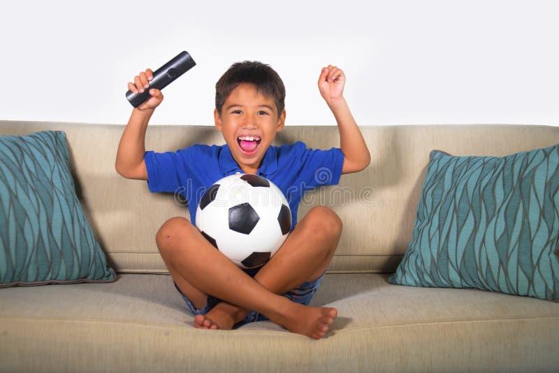 Młodej latynoskiej chłopiec szczęśliwy i z podnieceniem dopatrywanie mecz futbolowy na telewizi żyje izbową leżanki odświętność z zdjęcie royalty free