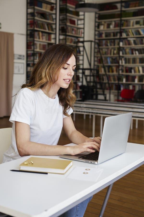 Młodej mądrze kobiety długie włosy analityk pracuje przy działania biurem na laptopie, półka na książki w bibliotece zdjęcie royalty free