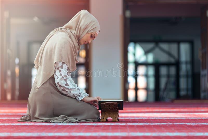 Młodej muzułmańskiej kobiety czytelniczy koran w meczecie obraz stock