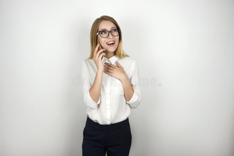 Młodej pięknej blondynki biznesowa kobieta w eyeglasses otrzymywał dobre wieści od partnera biznesowego podczas znacząco telefonu obrazy stock