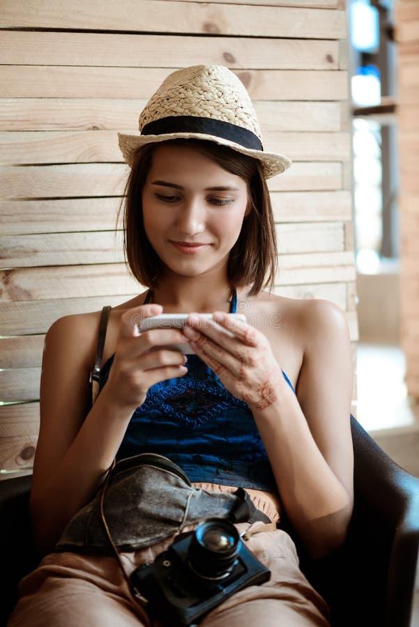 Młodej pięknej brunetki żeński fotograf patrzeje telefon, ono uśmiecha się obrazy royalty free