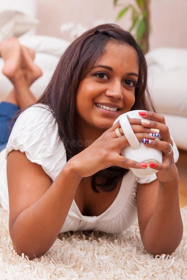 Młodej pięknej indyjskiej kobiety pije kawa obrazy stock