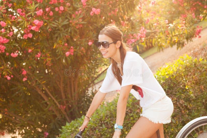 Młodej pięknej kobiety jeździecki bicicle na lecie fotografia royalty free