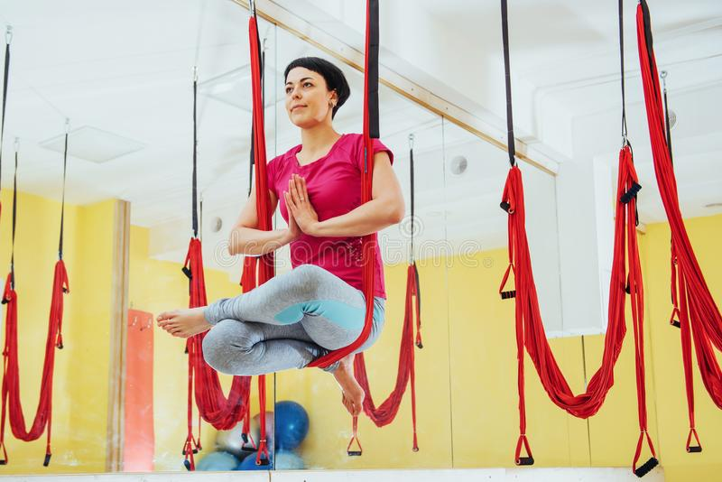Młodej pięknej kobiety joga ćwiczy komarnica z hamakiem w jaskrawym studiu Pojęcie umysłowi i fizyczni zdrowie obraz stock