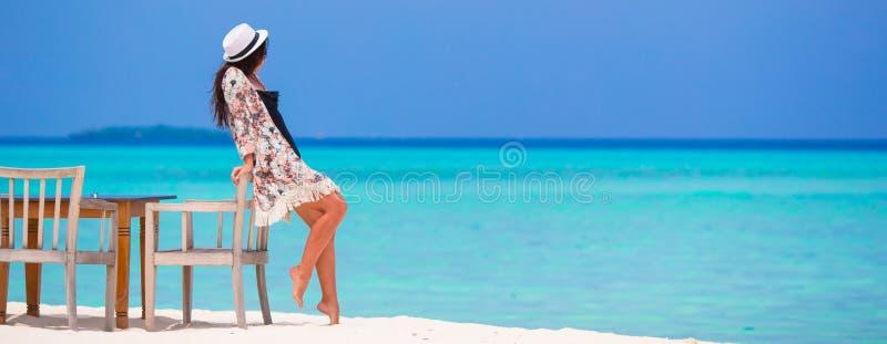 Młodej pięknej kobiety pobliska plażowa kawiarnia podczas ona zdjęcie royalty free