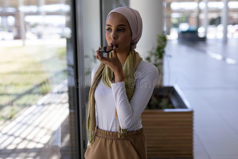Młodej rasy żeński kierownictwo opowiada na telefonie komórkowym w nowożytnym biurze fotografia stock