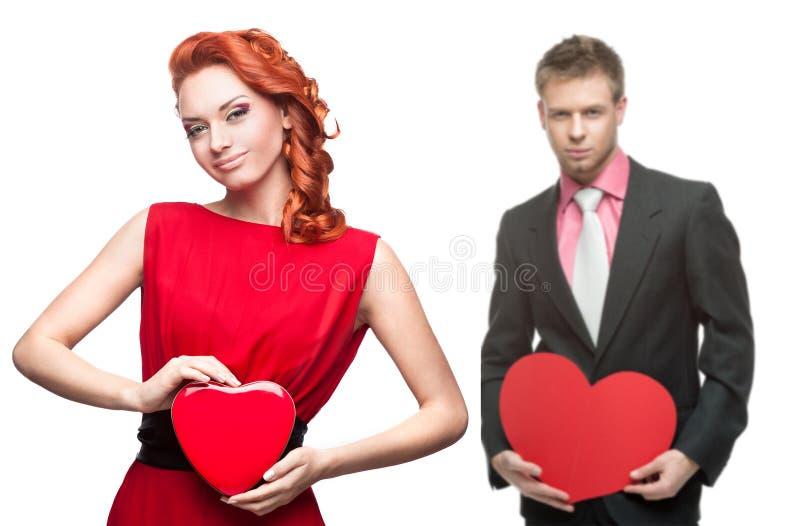 Młodej rozochoconej kobiety i przystojnego mężczyzna mienia czerwony serce na bielu fotografia royalty free