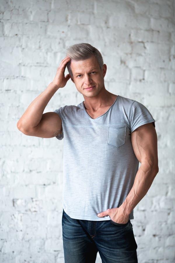 Młodej seksownej mężczyzna bodybuilder atlety pracowniany portret w loft na tle biały ściana z cegieł Przystojny faceta model wew obraz stock