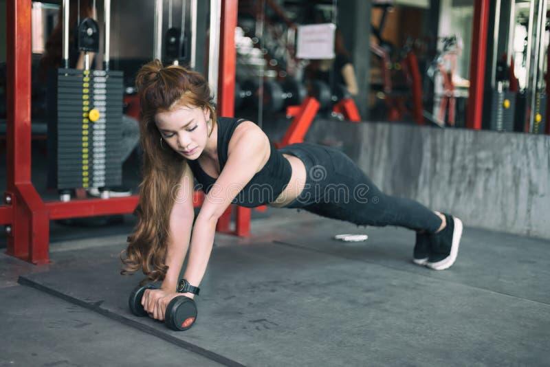Młodej sprawności fizycznej kobiety azjatykci ćwiczenie i robić deski pozyci z obrazy stock