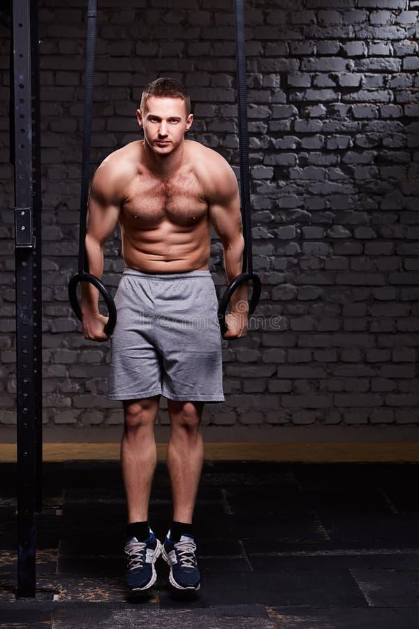 Młodej sprawności fizycznej przystojny mężczyzna robi maczania ćwiczeniu używa pierścionki przeciw ściana z cegieł w krzyżuje dys zdjęcia stock
