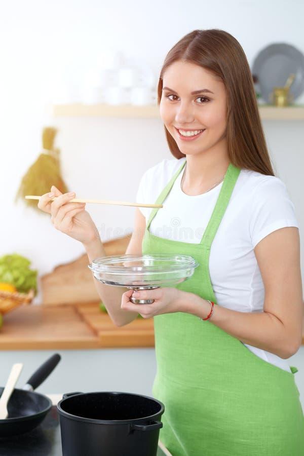 Młodej szczęśliwej kobiety kulinarna polewka w kuchni Zdrowy posiłek, styl życia i kulinarny pojęcie, uśmiechnięty dziewczyna ucz obrazy royalty free