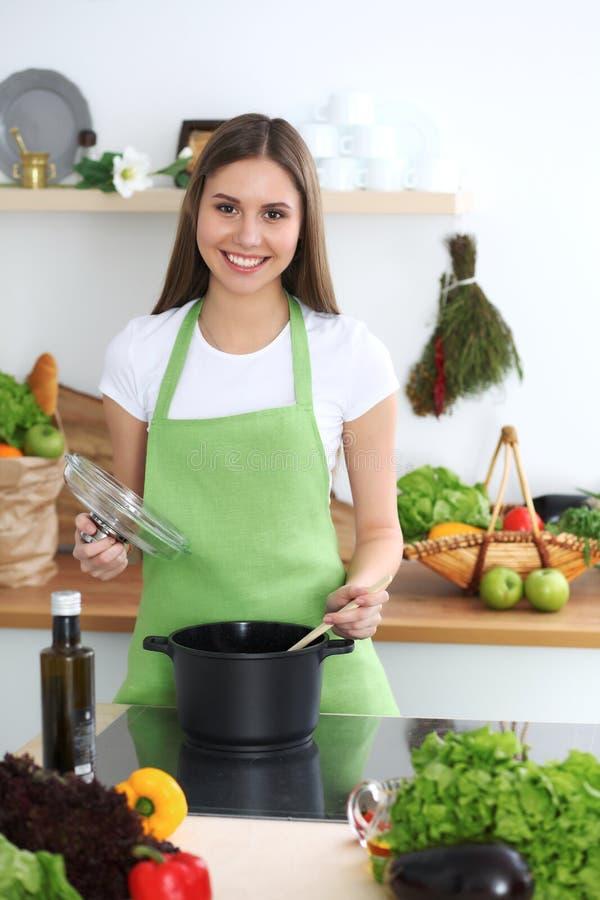 Młodej szczęśliwej kobiety kulinarna polewka w kuchni Zdrowy posiłek, styl życia i kulinarny pojęcie, uśmiechnięty dziewczyna ucz fotografia royalty free