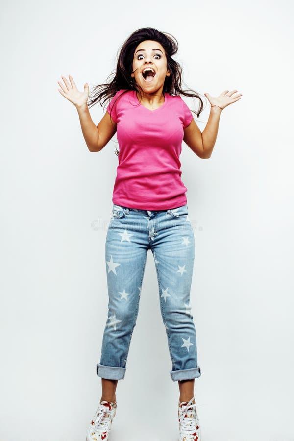 Młodej szczęśliwej uśmiechniętej latyno-amerykański nastoletniej dziewczyny emocjonalny pozować na białym tle, skokowy latanie w  zdjęcia stock