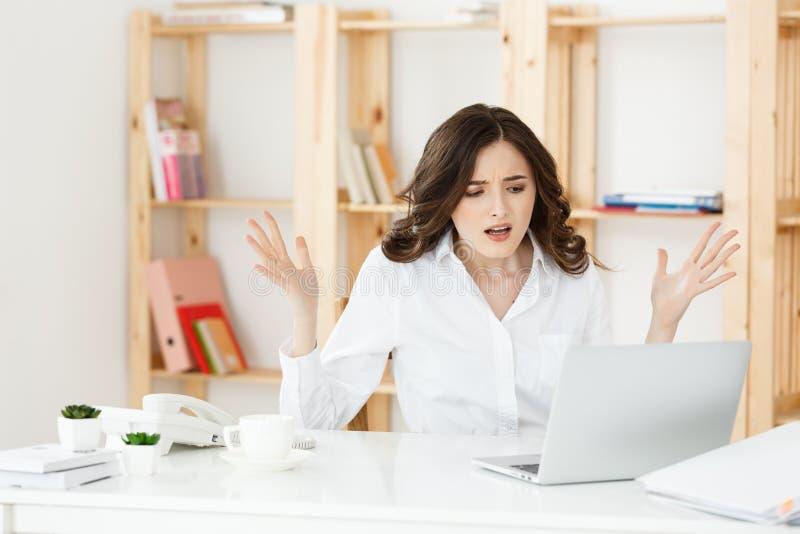 Młodej właściciela małego biznesu kobiety przyglądający labtop i odczucie migrena z jej biznesowymi stratami, Biznesowych strat p zdjęcia royalty free