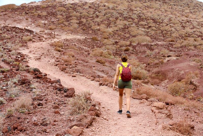 Młodej wycieczkowicz kobiety wspinaczkowa góra z czerwienią gruntuje w Tenerife zdjęcia stock
