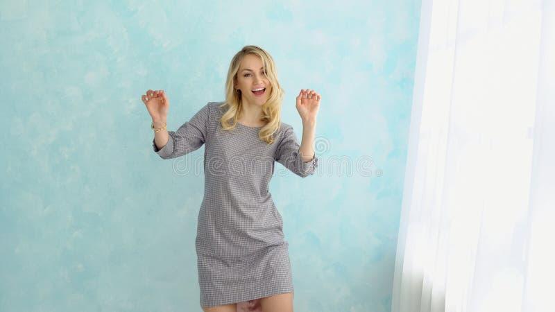 Młodej zabawy piękna kobieta w szarej sukni tanczy obok okno obrazy royalty free