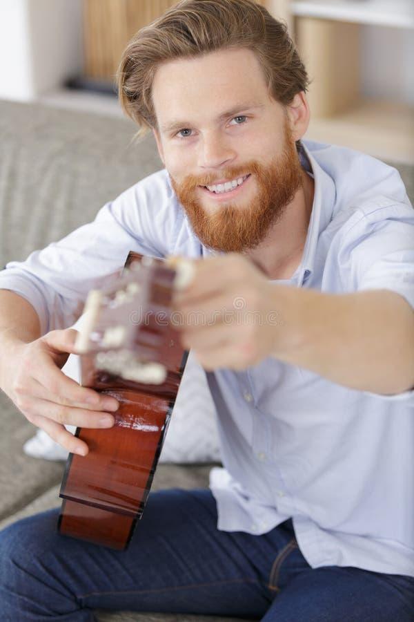 Młodość mężczyzna bawić się gitarę akustyczną na kanapie zdjęcie royalty free