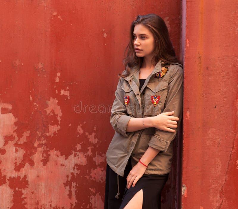 Młodości ładna kobieta na ulicznej pobliskiej czerwieni ścianie fotografia stock