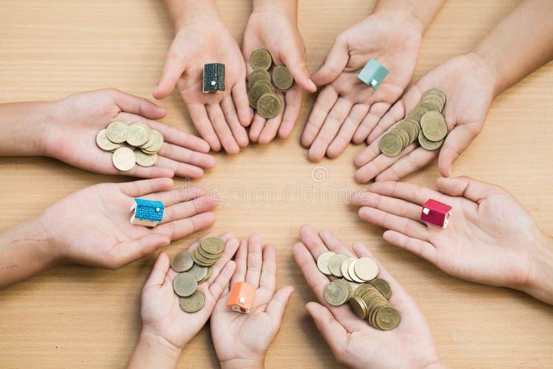 Młodości przedstawienia ręka trzyma wzorcowego dom i drewniany bac moneta zdjęcie stock