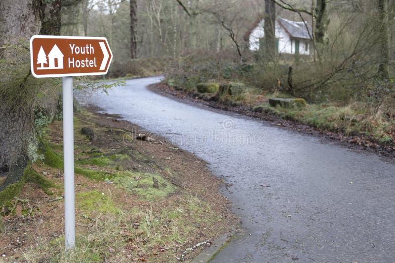 Młodości schroniska znaka kierunku wiodąca droga bothy hotel dla piechurów turystów w lasowej drewno wsi zdjęcie stock