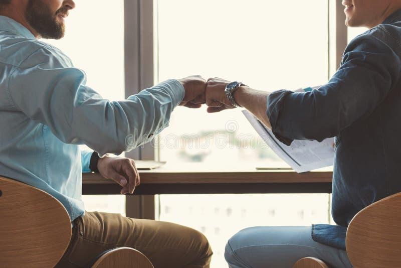 Młodociani faceci komunikuje wpólnie podczas gdy pracujący w biurze fotografia stock