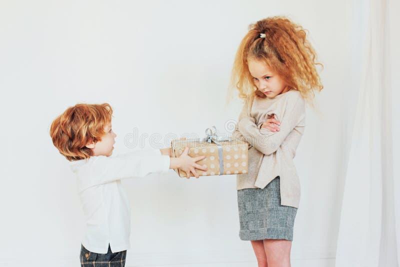 Młodszy brat daje jego siostrzanemu prezentowi, ale obraża zdjęcie stock