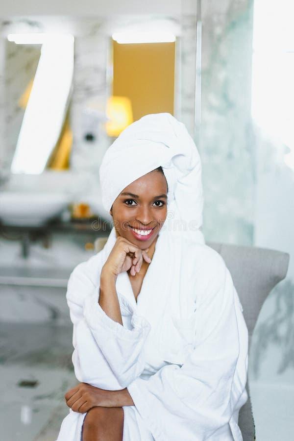 Młody ładny afro amerykański dziewczyny obsiadanie w łazience i być ubranym białego bathrobe obrazy royalty free