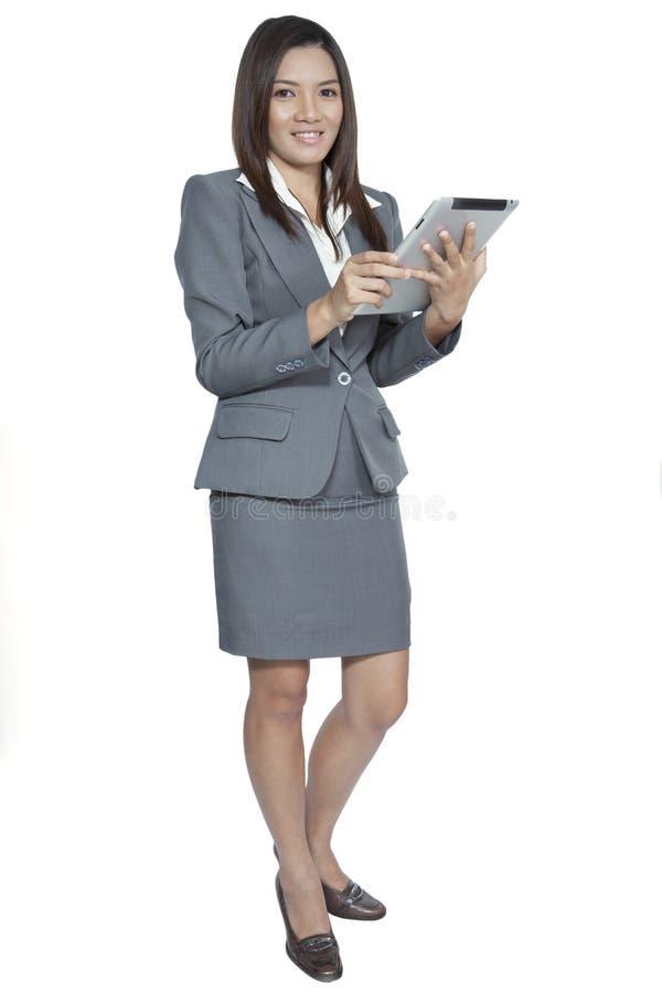 Młody ładny Azjatycki biznesowej kobiety gest używać pastylki ono uśmiecha się obrazy stock