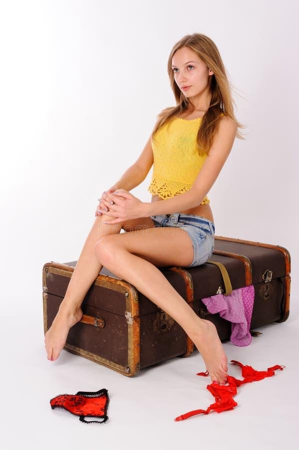 Młody ładny kobiety obsiadanie na rocznik walizce obrazy stock