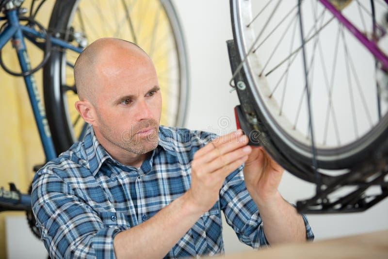 Młody łysy mężczyzny naprawiania bicykl zdjęcie stock