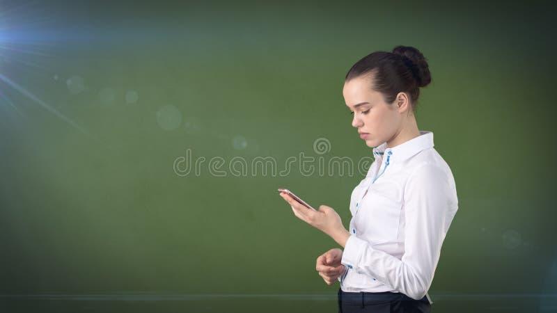 Młody śliczny bizneswomanu zakończenie w górę portreta mienia telefonu komórkowego w ona ręki i dopatrywanie ja Odosobniony praco zdjęcie royalty free