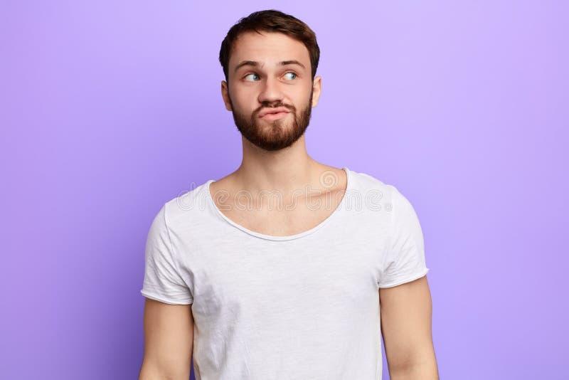 Młody śmieszny brodaty atrakcyjny mman z skeptic spojrzeniem, niektóre wątpienia zdjęcia stock