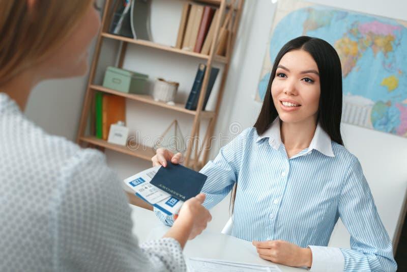 Młody żeński agenta biura podróży konsultant w wycieczki turysycznej agenci z klienta biletami i paszportami zdjęcia stock