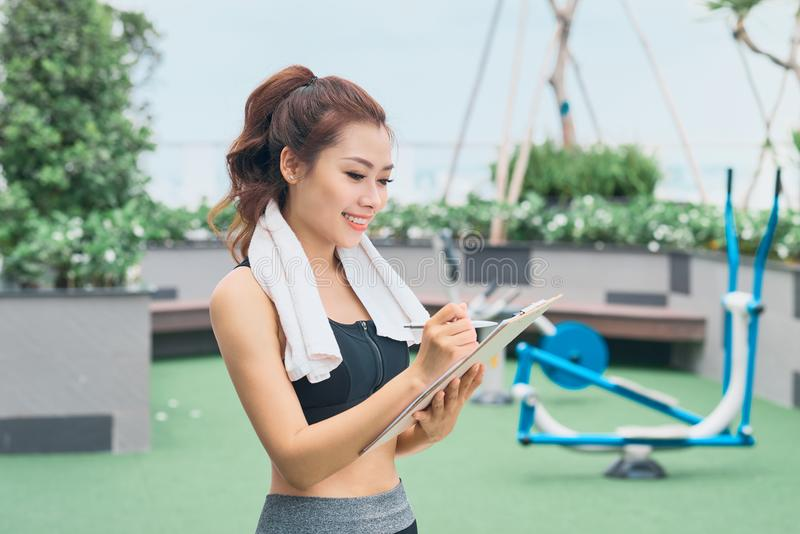 Młody żeński azjatykci trener bierze notatki outdoors fotografia royalty free