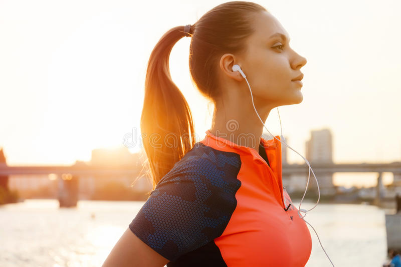 Młody żeński biegacz jogging nad zmierzchem, rzeki strona, miastowy miasto co obraz royalty free