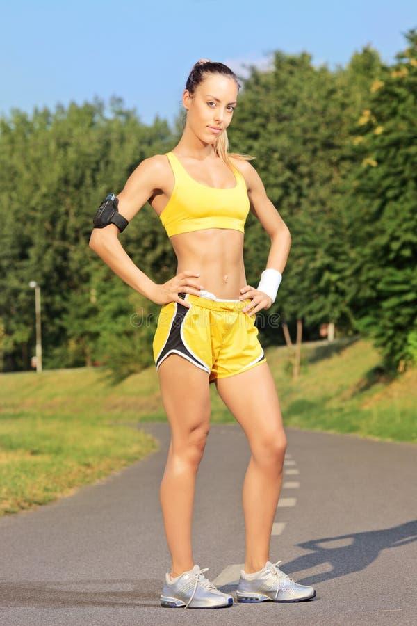 Młody żeński biegacz pozuje na działającym śladzie w parku fotografia stock