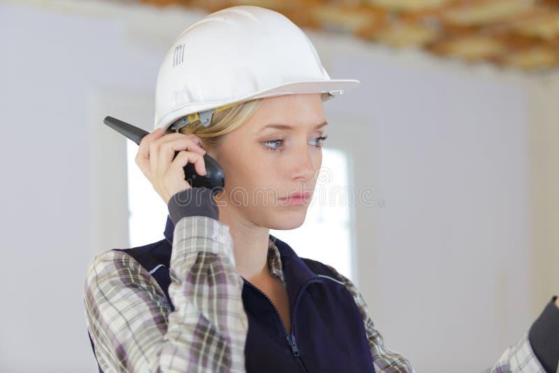 Młody żeński budowniczy słucha walkie talkie odbiorca obraz stock