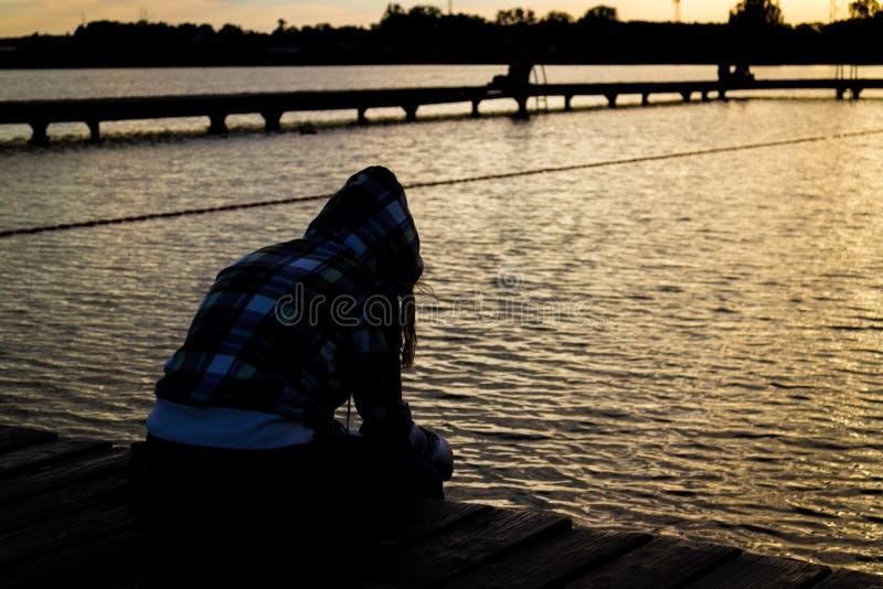 Młody żeński dziewczyny obsiadanie na drewnianym molu w zmierzchu patrzeje wodę obraz stock