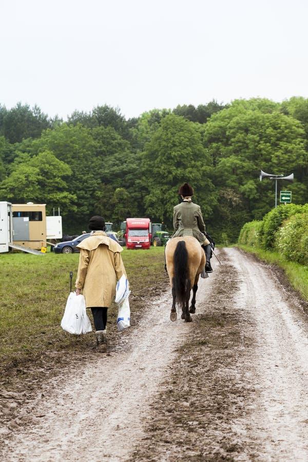 Młody żeński equestrian jedzie jej końskiego puszka kraju błotnistego pas ruchu zdjęcia stock