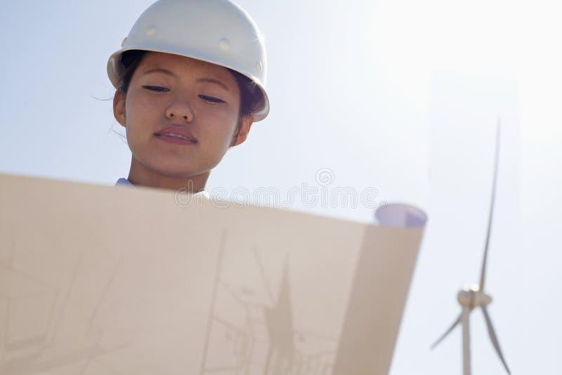 Młody żeński inżyniera mienie otwarty i patrzeje w dół przy projektami, na miejscu z silnikami wiatrowymi obrazy stock