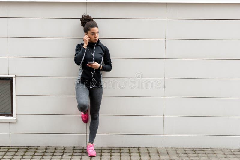 Młody żeński jogger z słuchawkami fotografia royalty free