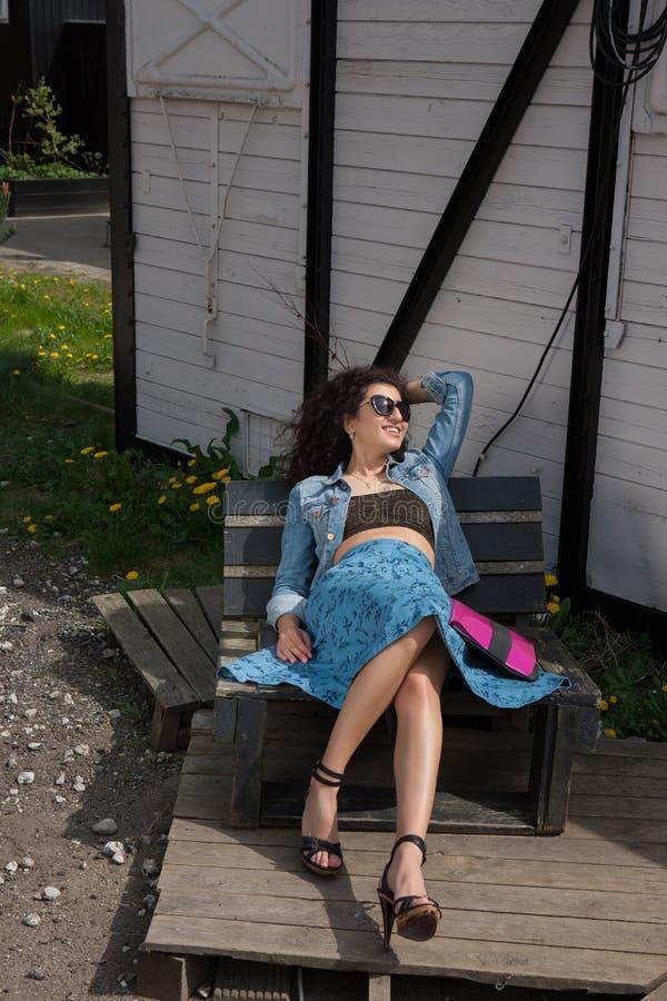 Młody żeński lying on the beach na ławce z okularami przeciwsłonecznymi zdjęcia royalty free