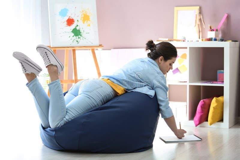 Młody żeński malarz na beanbag krześle w studiu fotografia stock