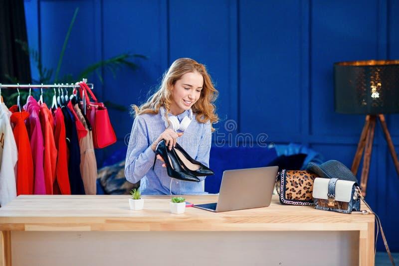 Młody żeński mody blogger przedstawia parę buty kamera zdjęcie royalty free